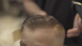Friseur, der kleinen Jungen und Ausschnitt des nass Haares mit elektrischem Rasiermesser im Friseursalon kämmt Herrenfriseur, der stock video footage