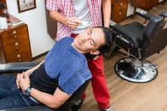 Friseur, der Mann ` s Bart sich entspannt auf Stuhl rasiert lizenzfreie stockfotografie