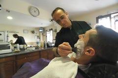 Friseur, der mit der Bürste rasiert Schaum zum jungen Mann sich rasiert Stockbild