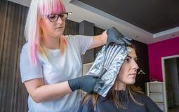 Friseur, der Stränge des Frauenhaares mit trennt Stockfoto