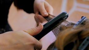 Friseur, der Strecker auf langem Haar des Kunden im Friseursalon verwendet Stockfoto