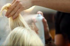 Friseur gesprühtes blondes Haar durch Spray Stockfotografie