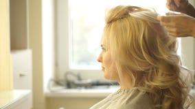 Friseur macht Abendfrisurnahaufnahme auf blondem Haar der Geschäftsfrau im Schönheitssalon stock footage