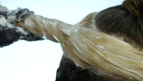 Friseur macht Frisur, Färbung für einen Jugendlichen in einem Schönheitssalon Haar bedeckt in der Färbung Langsame Bewegung stock footage