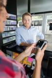 Friseur mit dem männlichen Kunden, der über elektronischem Leser am Zähler zahlt lizenzfreies stockbild