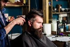 Friseur mit Haarscherer arbeitet an Frisur für Mann mit Bart, Friseursalonhintergrund Friseur, der Haar von bärtigem anredet Lizenzfreies Stockbild