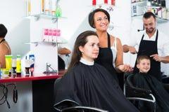 Friseur mit Kunden im Schönheitssalon stockbilder