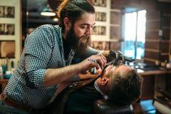 Friseur rasiert Bart des Kunden, indem er Blatt rasiert Stockfotografie