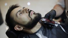 Friseur rasiert den Bart des Kunden mit Trimmer stock video