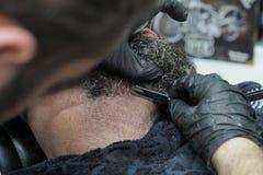 Friseur rasiert den Bart eines älteren Mannes mit scharfem Rasiermesser des grauen Haares stockfotos