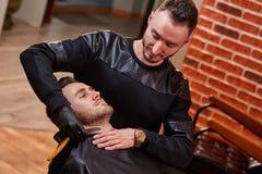 Friseur rasiert männlichen Bart mit dem Messer gegen Backsteinmauer am Friseursalon Lizenzfreies Stockbild