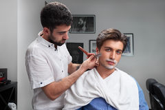 Friseur rasiert sorgfältig den Bart des Kunden mit Rasiermesser Lizenzfreie Stockbilder