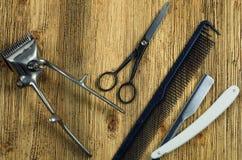 Friseur ` s Werkzeuge auf einer Holzoberfläche Stockfotografie