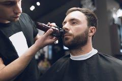 Friseur schneidet einen Bart zu einem Mann in einem Friseursalon Stockbilder