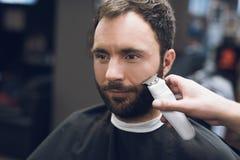 Friseur schneidet einen Bart zu einem Mann in einem Friseursalon Lizenzfreies Stockbild
