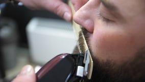 Friseur schneidet Kundenbart mit einem Berufsbarttrimmer in einem Friseursalon auf hellem Hintergrund, Nahaufnahme Langsame Beweg stock video