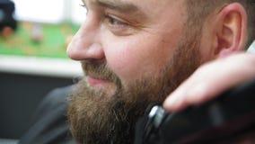 Friseur schneidet Kundenbart mit einem Berufsbarttrimmer in einem Friseursalon auf hellem Hintergrund, Nahaufnahme Langsame Beweg stock footage
