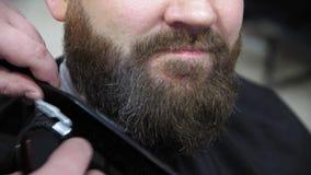 Friseur schneidet Kundenbart mit einem Berufsbarttrimmer in einem Friseursalon, Nahaufnahme stock video footage
