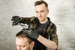 Friseur schnitt Haar und k?mmt erwachsenen Mann auf einem Backsteinmauerhintergrund Nahes hohes Portr?t eines Kerls lizenzfreie stockbilder