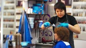 Friseur setzt Farbe auf das Haar stock footage