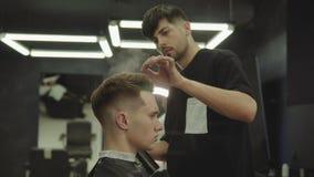 Friseur stellt das Haar her, das mit Haarspray nach Haarschnitt am Friseursalon anredet Junger h?bscher kaukasischer Mann, der a  stock footage