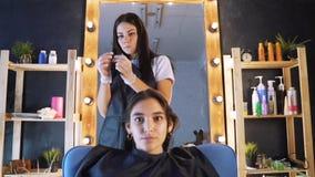Friseur, Stilist, der Haar des weiblichen Kunden kämmt und Haarspange für Reparierenfrisur im Berufsfriseursalon verwendet stock footage