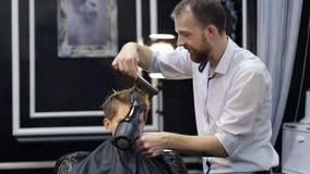 Friseur trocknet Haarjugendlichen mit einem Haartrockner stock video
