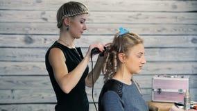 Friseur tut eine Frisur für ein Mädchen stock footage