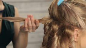 Friseur tut eine Frisur für ein Mädchen stock video