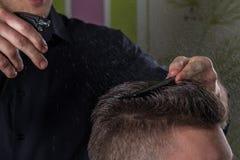 Friseur tut Haar mit Wasser und Kamm des Kunden im Berufsfrisörsalon lizenzfreie stockfotos