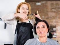 Friseur tut zum Frauenhaarschnitt mit Gebrauch von Scheren und hairb Lizenzfreies Stockfoto