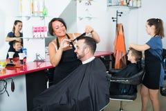 Friseur und Kunde im Schönheitssalon lizenzfreie stockbilder