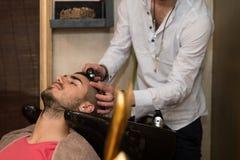 Friseur Washing Man Head in Barber Shop Stockbilder