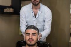 Friseur Washing Man Head in Barber Shop Lizenzfreie Stockfotos