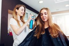 Friseurfestlegungsfrisur des lächelnden weiblichen Kunden mit Haarspray im Frisurnschönheitssalon stockbilder
