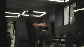 Friseurfriseur bereitet sich für den folgenden Kunden vor, der ein Kap des schwarzen Haares im Innenraum faltet Handschu? 4K stock footage