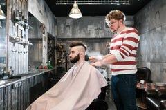 Friseurmann rasiert einen Kunden mit einem Bart in einem Friseursalon Lizenzfreie Stockbilder