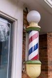Friseurpfosten außerhalb des Geschäftsfensters stockfotografie