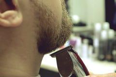 Friseurrasuren trotzen vom Kundenmann auf Stuhl Friseursalon Bart-Haarschnitt Friseur, der Bart mit Elektrorasierer in Weinlesefr stockfotos