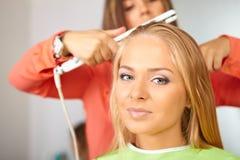 Friseursalon. Frauen ` s Haarschnitt. Gebrauch des Streckers. stockfoto