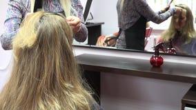 Friseursarbeit über blondes Frauenhaar im Salon nahaufnahme 4K stock footage