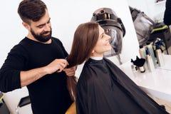 Friseurstilist kämmt junge Frau mit dem braunen Haar mit Haarbürste stockfotos