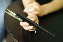Friseurwerkzeuge in den Händen eines Berufs-, langen Haares, der Scheren und des Kammes in seinem Handfriseur Stockfoto