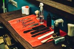 Friseurwerkzeuge Seitenansicht des Friseursalons bearbeitet das Lügen auf dem hölzernen Korn Stockfotografie