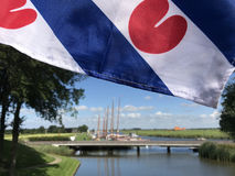Frisian flag with skutsjes in the background. In Sloten, Friesland, The Netherlands Stock Photo