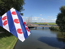 Frisian flag with skutsjes in Sloten. Frisian flag with skutsjes in the background in Sloten, Friesland, The Netherlands Royalty Free Stock Images