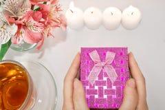 Frisierkommode mit Blumen, einer Tasse Tee, Kerzen und Frauen ` s übergibt das Halten einer Geschenkbox lizenzfreie stockfotografie