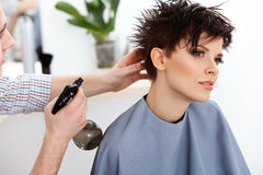 Frisör som gör frisyren Brunett med kort hår i salong Royaltyfria Bilder