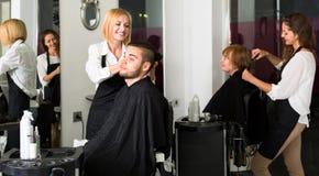 Frisörer med sax som klipper hår Arkivbild