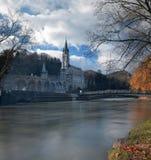 Fristäder av Lourdes från gränsen av Gave de Pau River fotografering för bildbyråer